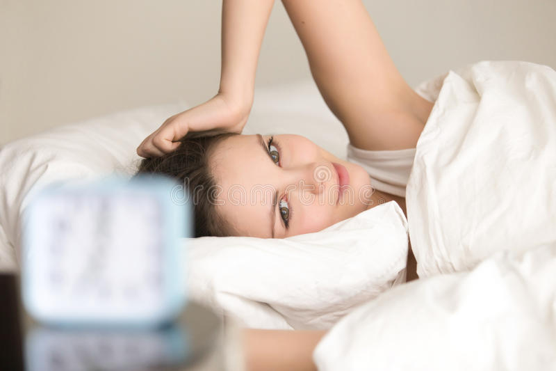 Glimlachende jonge vrouw die wakker in bed, gelukkige ontwaken liggen royalty-vrije stock foto's