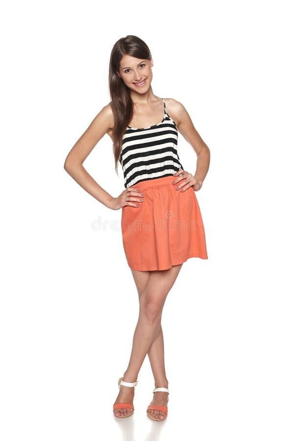Glimlachende jonge vrouw die zich in de zomerkleding bevinden royalty-vrije stock foto
