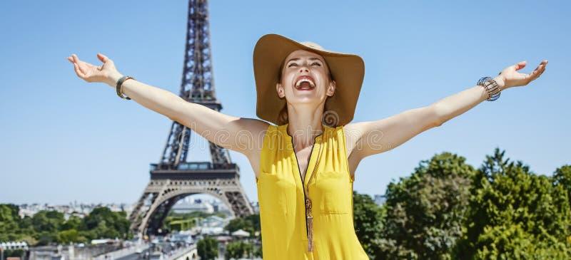 Glimlachende jonge vrouw die zich voor de toren van Eiffel in Parijs verheugen royalty-vrije stock fotografie
