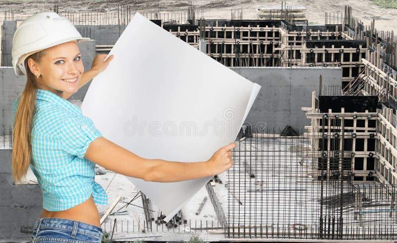 Glimlachende jonge vrouw in het document van de bouwvakkerholding stock afbeelding
