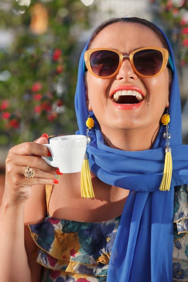 Glimlachende jonge vrouw het drinken koffie stock afbeelding