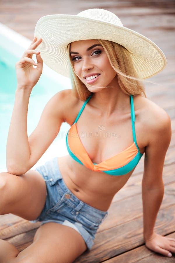 Glimlachende jonge vrouw in hoed en borrels dichtbij zwembad royalty-vrije stock afbeeldingen