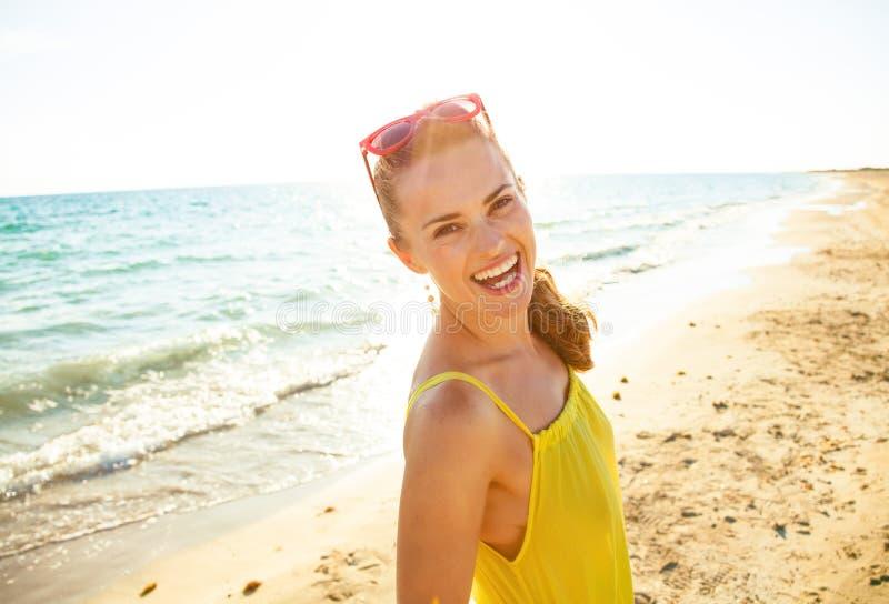 Glimlachende jonge vrouw in kleurrijke kleding op kust in avond stock fotografie