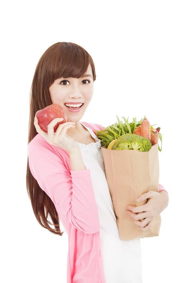 Glimlachende jonge vrouw met appel en groenten stock foto's