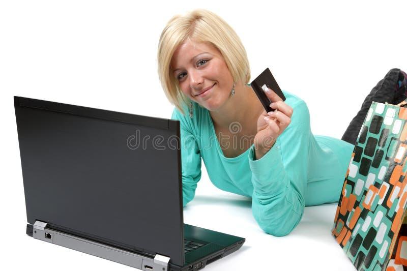Glimlachende jonge vrouw met creditcard die laptop met behulp van stock foto