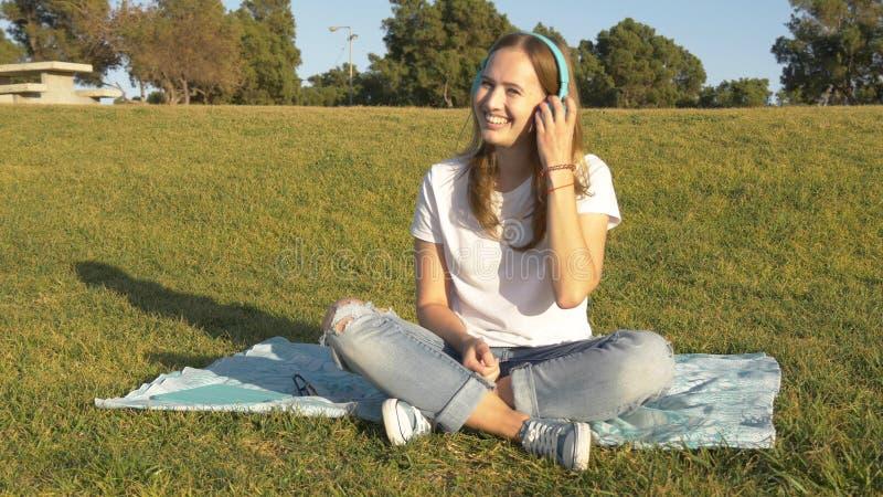 Glimlachende jonge vrouw met draadloze hoofdtelefoonszetel op groen gras royalty-vrije stock afbeelding