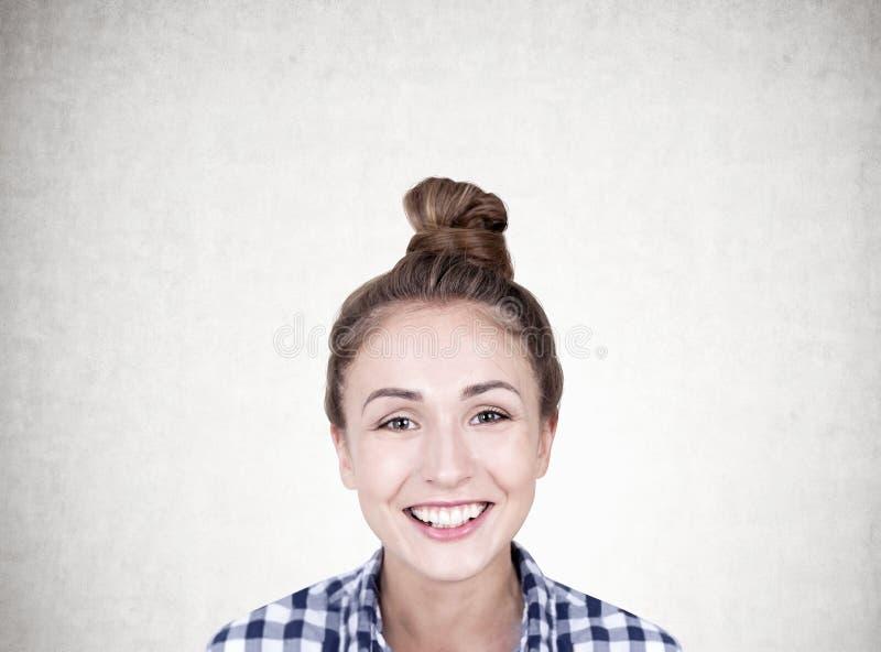 Glimlachende jonge vrouw met een concreet broodje, royalty-vrije stock fotografie