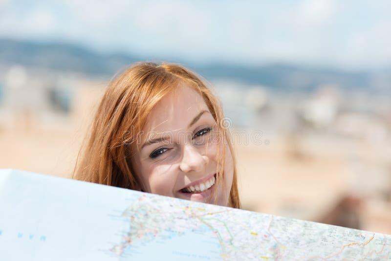 Glimlachende jonge vrouw met een kaart royalty-vrije stock foto