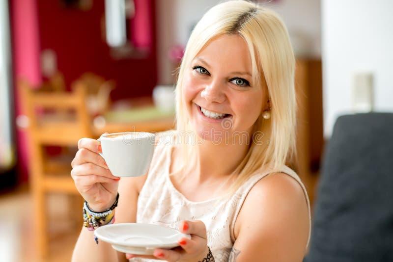 Glimlachende jonge vrouw met een koffiekop stock foto's