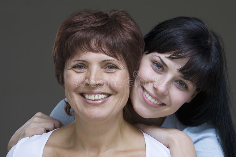 Glimlachende Jonge Vrouw met Haar Moeder stock foto