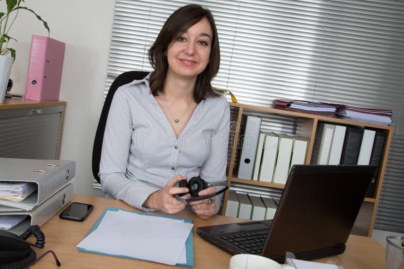 Glimlachende jonge vrouw met hoofdtelefoons en laptop op de bank stock foto's