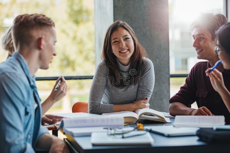 Glimlachende jonge vrouw met klasgenoten in bibliotheek royalty-vrije stock afbeeldingen