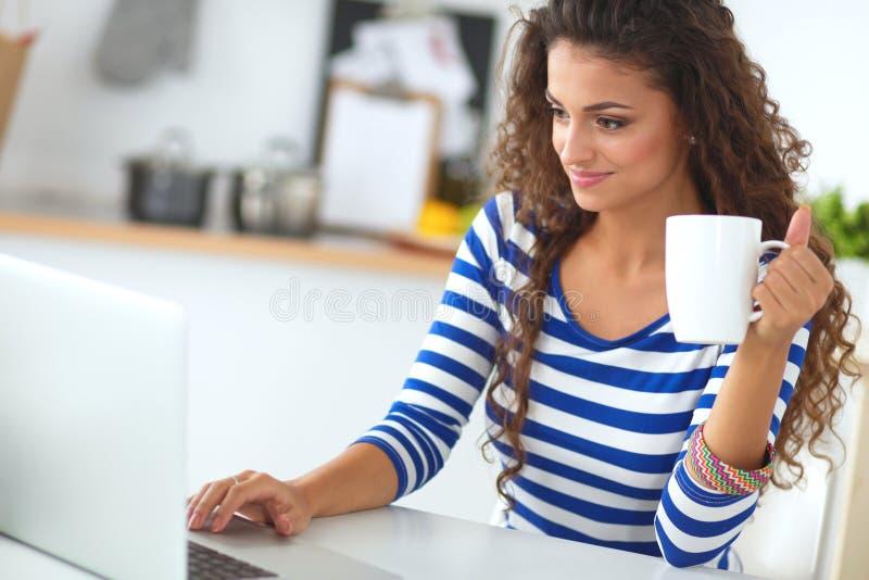 Glimlachende jonge vrouw met koffie binnen kop en laptop stock afbeelding