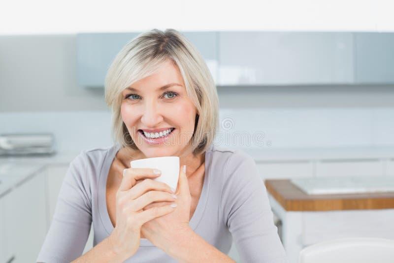 Glimlachende jonge vrouw met koffiekop in keuken thuis stock foto