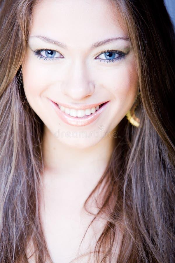Glimlachende jonge vrouw met lang recht haar stock foto