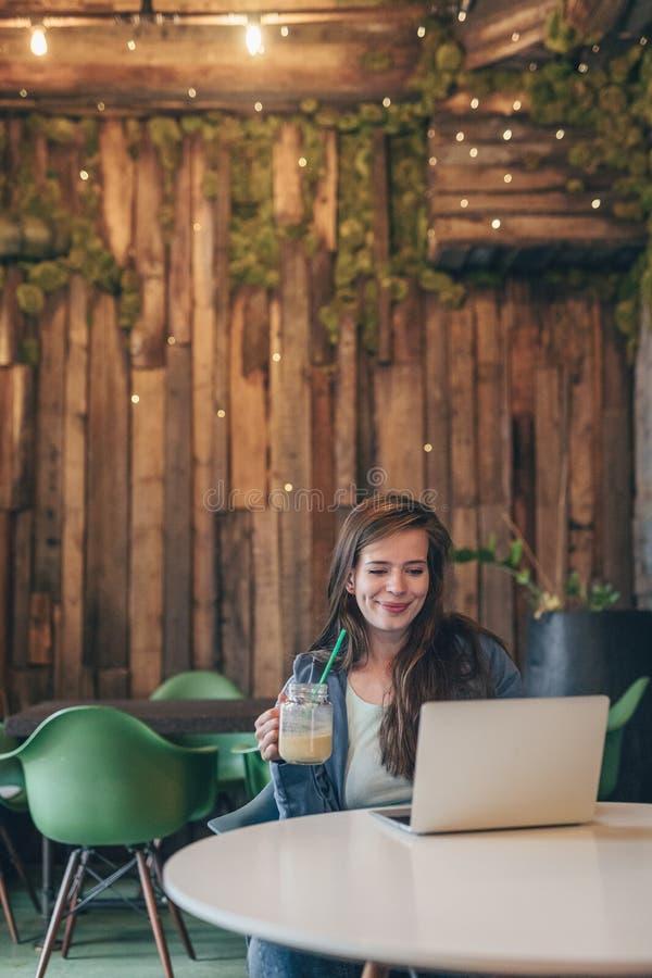 Glimlachende jonge vrouw met laptop stock afbeeldingen
