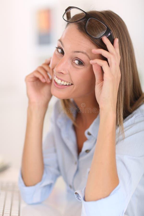 Glimlachende jonge vrouw met oogglazen stock afbeelding