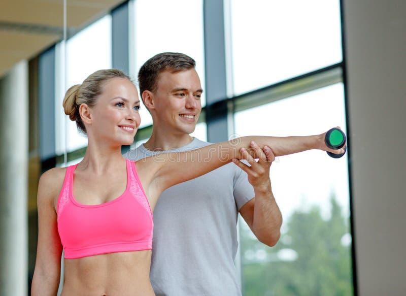 Glimlachende jonge vrouw met persoonlijke trainer in gymnastiek stock foto