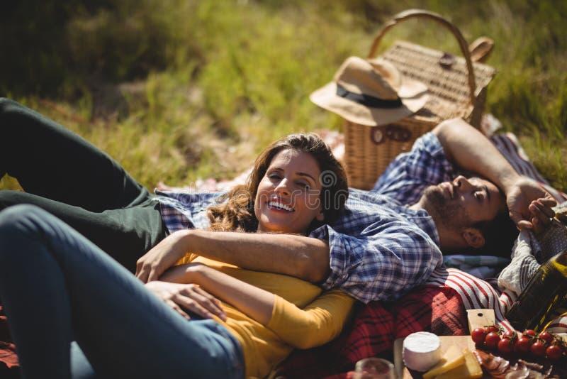 Glimlachende jonge vrouw met vriend het ontspannen op picknickdeken bij olijflandbouwbedrijf stock afbeelding