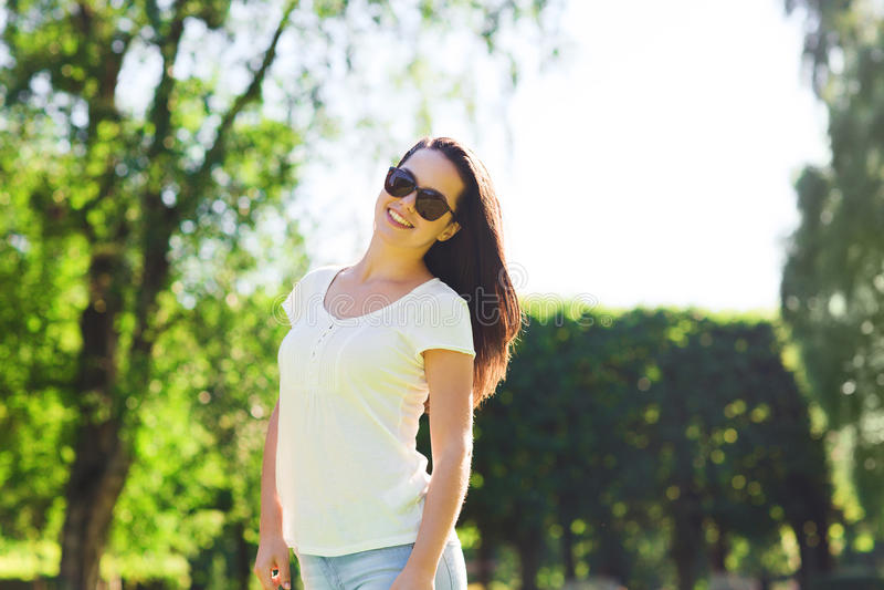 Glimlachende jonge vrouw met zonnebril in park stock foto