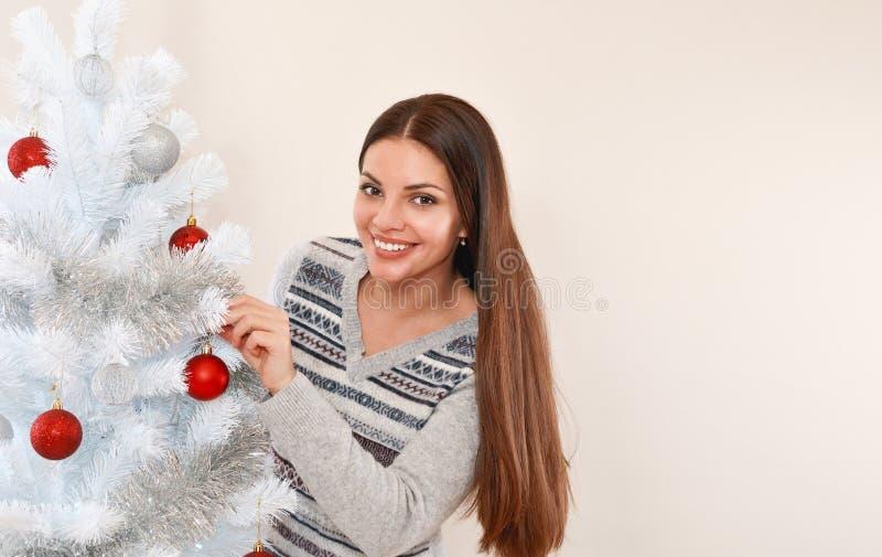 Glimlachende jonge vrouw naast witte Kerstmisboom stock afbeeldingen