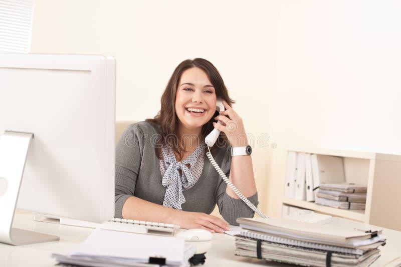 Glimlachende jonge vrouw op de telefoon op kantoor stock foto's