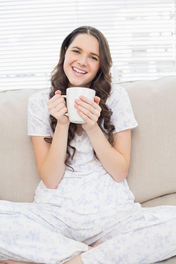 Glimlachende jonge vrouw in pyjama die koffie hebben royalty-vrije stock afbeeldingen