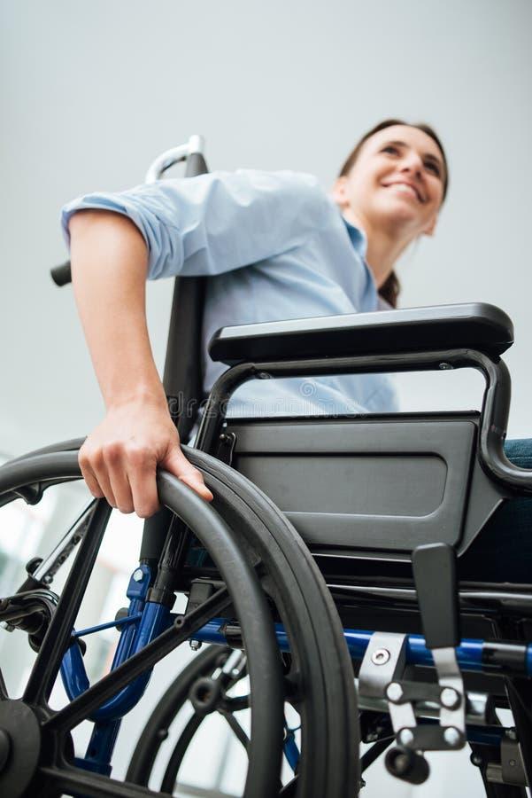 Glimlachende jonge vrouw in rolstoel stock foto