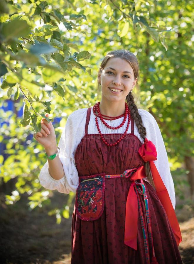 Glimlachende jonge vrouw in Russisch volkskostuum op de gebladerteachtergrond stock foto