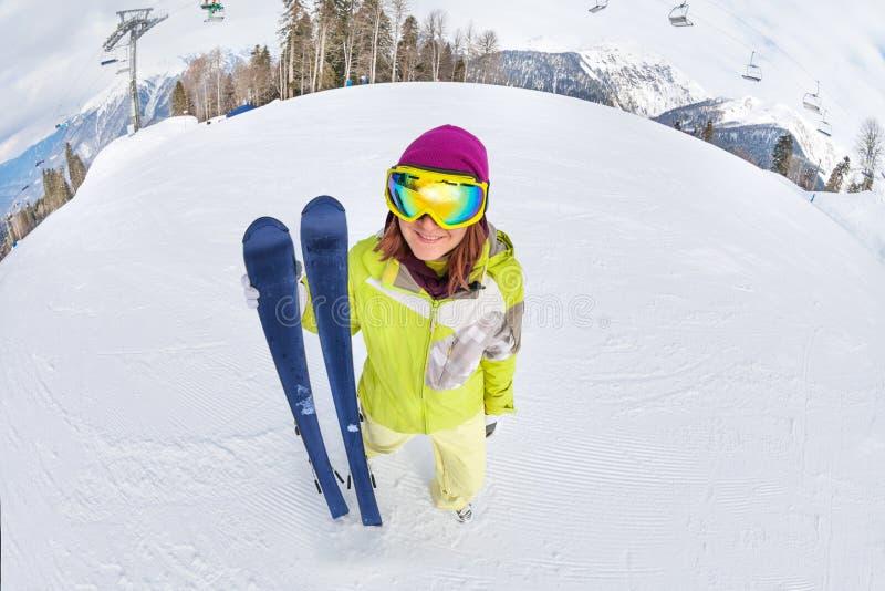 Glimlachende jonge vrouw in skimasker op sneeuwbergen royalty-vrije stock foto's