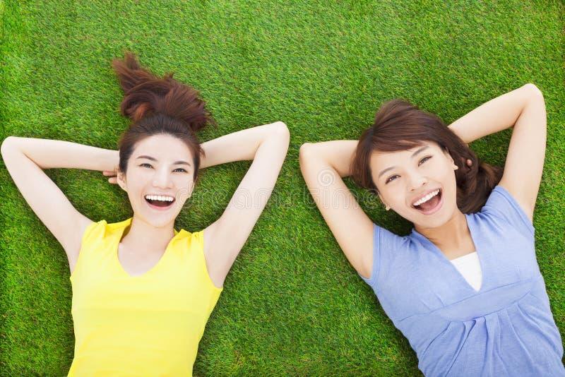 Glimlachende jonge vrouw twee die op weide liggen royalty-vrije stock foto's