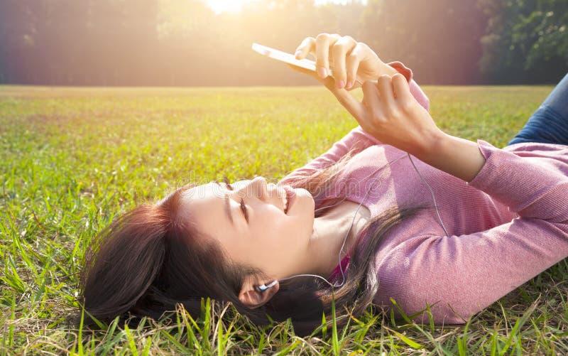 Glimlachende jonge vrouw wat betreft celtelefoon en het liggen op weide stock afbeeldingen