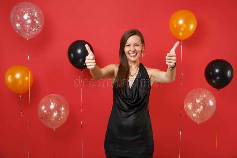 Glimlachende jonge vrouw in weinig het zwarte kleding vieren, die duimen op heldere rode achtergrondluchtballons tonen ST stock foto's