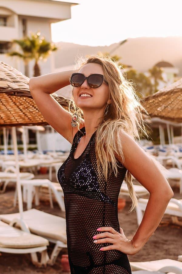 Glimlachende jonge vrouw in zonnebril die op het strand in de contouren aangegeven van zonlicht stellen royalty-vrije stock afbeelding