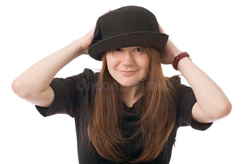 Glimlachende jonge vrouw in zwarte hoed stock afbeeldingen