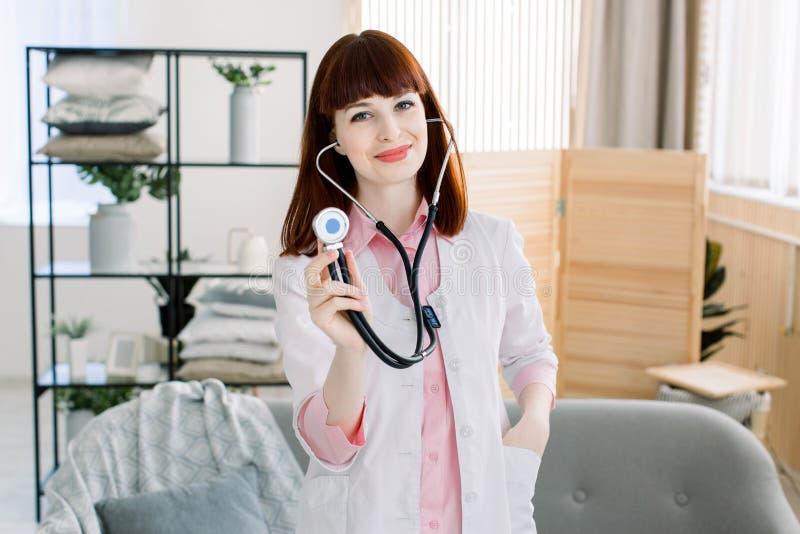 Glimlachende jonge vrouwelijke arts met stethoscoop op haar hals, vriendschappelijke positieve het bezoekcliënt die van de vrouwe royalty-vrije stock afbeelding