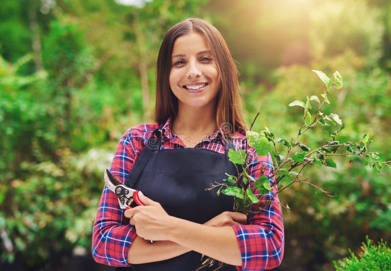 Glimlachende jonge vrouwelijke tuinman die de installaties snoeien stock afbeeldingen