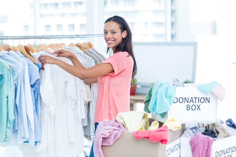 Glimlachende jonge vrouwelijke vrijwilliger die kleren scheiden stock afbeeldingen