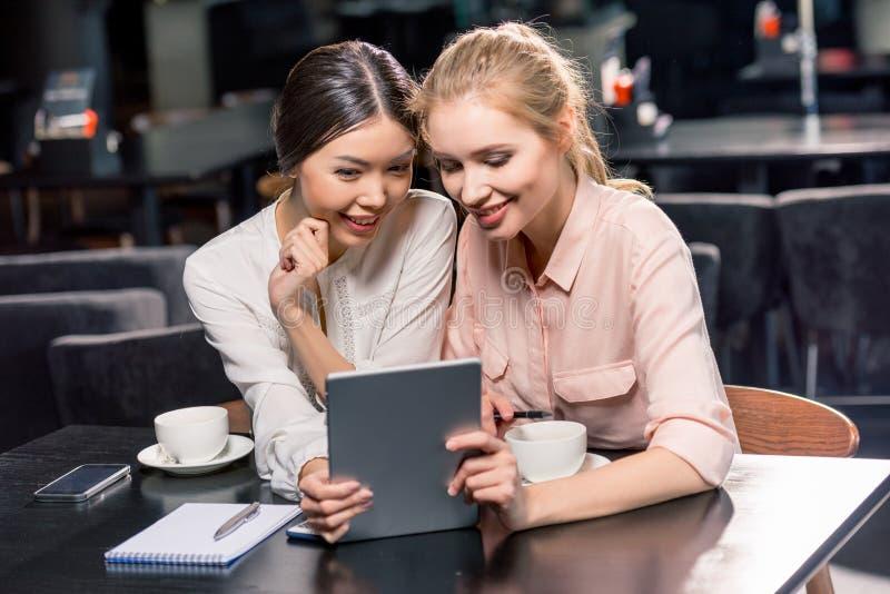 Glimlachende jonge vrouwen die digitale tablet gebruiken terwijl het drinken van koffie in koffie stock afbeeldingen