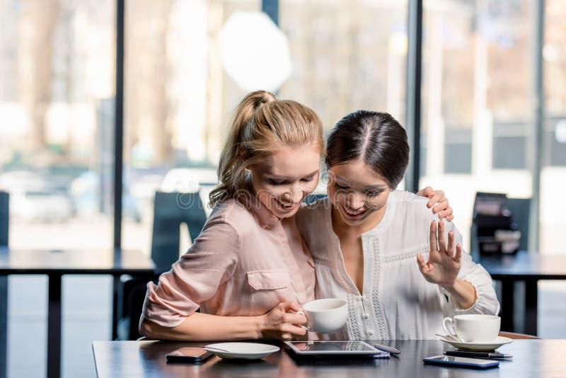 Glimlachende jonge vrouwen die digitale tablet gebruiken terwijl het drinken van koffie in koffie stock afbeelding