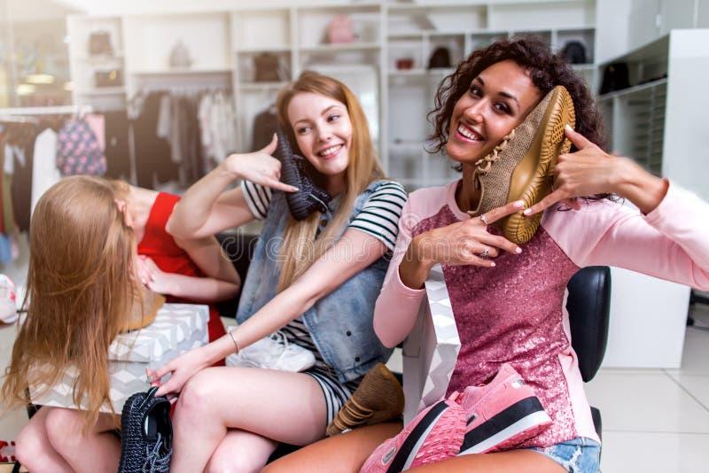 Glimlachende jonge vrouwen die in het womenswear opslag spelen met nieuw schoeisel zitten die schoenen zoals een telefoon gebruik royalty-vrije stock afbeelding