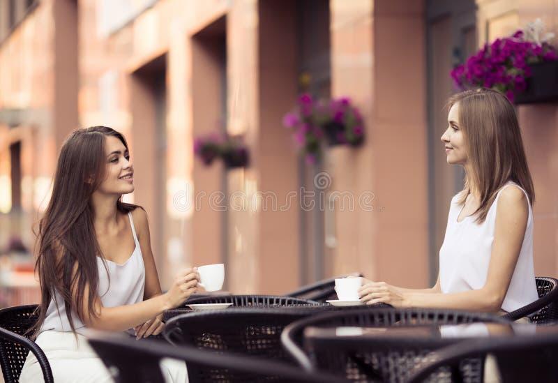 Glimlachende Jonge Vrouwen die Koffie drinken stock foto's