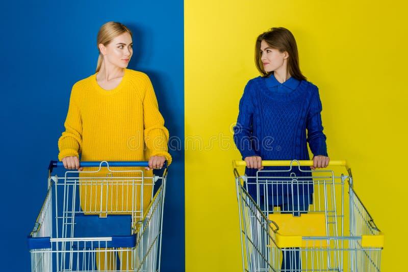 Glimlachende jonge vrouwen die met boodschappenwagentjes elkaar op blauw bekijken royalty-vrije stock afbeeldingen