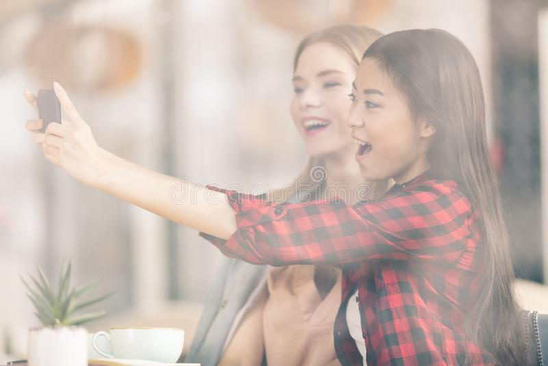 Glimlachende jonge vrouwen die smartphone gebruiken terwijl samen het drinken van koffie royalty-vrije stock foto's