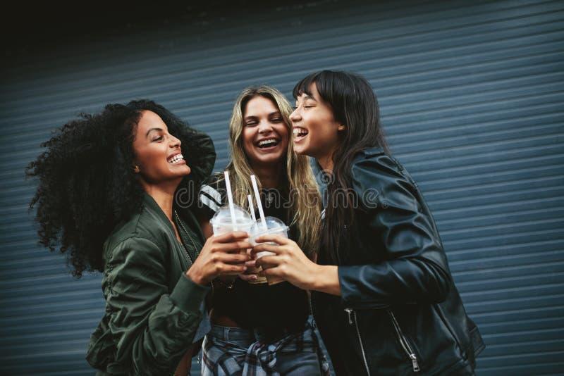 Glimlachende jonge vrouwen met ijskoffie stock foto