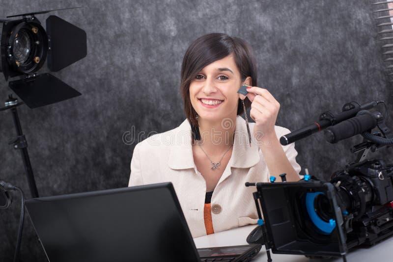 Glimlachende jonge vrouwen videoredacteur die een BR-kaart in studio tonen stock afbeeldingen