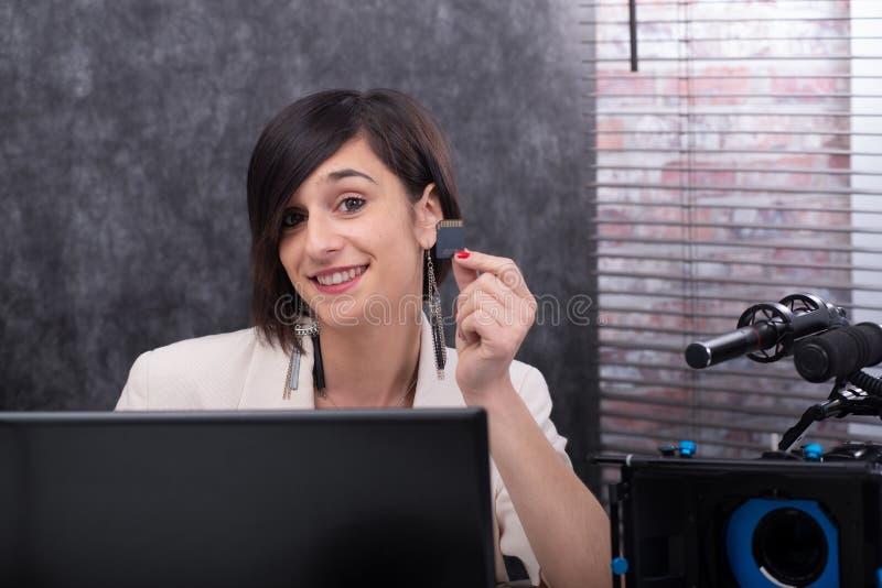 Glimlachende jonge vrouwen videoredacteur die een BR-kaart in studio tonen stock foto