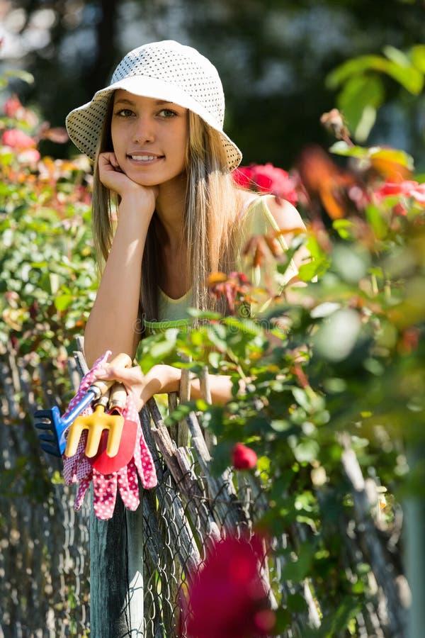 Glimlachende jonge vrouwenbloemisten in schort het werken stock fotografie