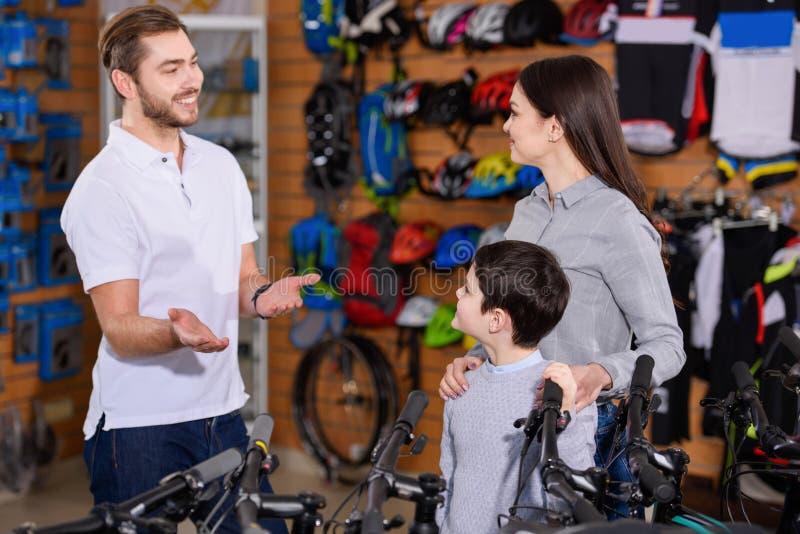 glimlachende jonge werknemer die fietsen tonen aan moeder en zoon royalty-vrije stock afbeeldingen