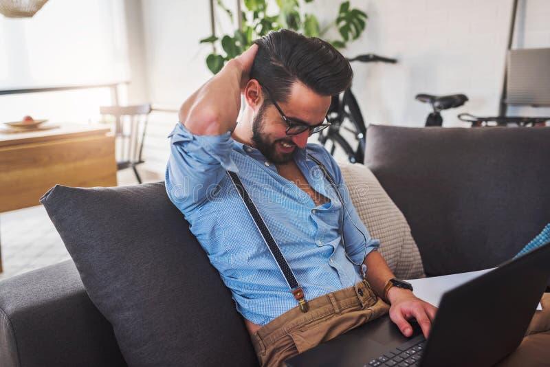 Glimlachende jonge zakenman die aan laptop computer werken terwijl thuis het zitten op bank royalty-vrije stock afbeeldingen